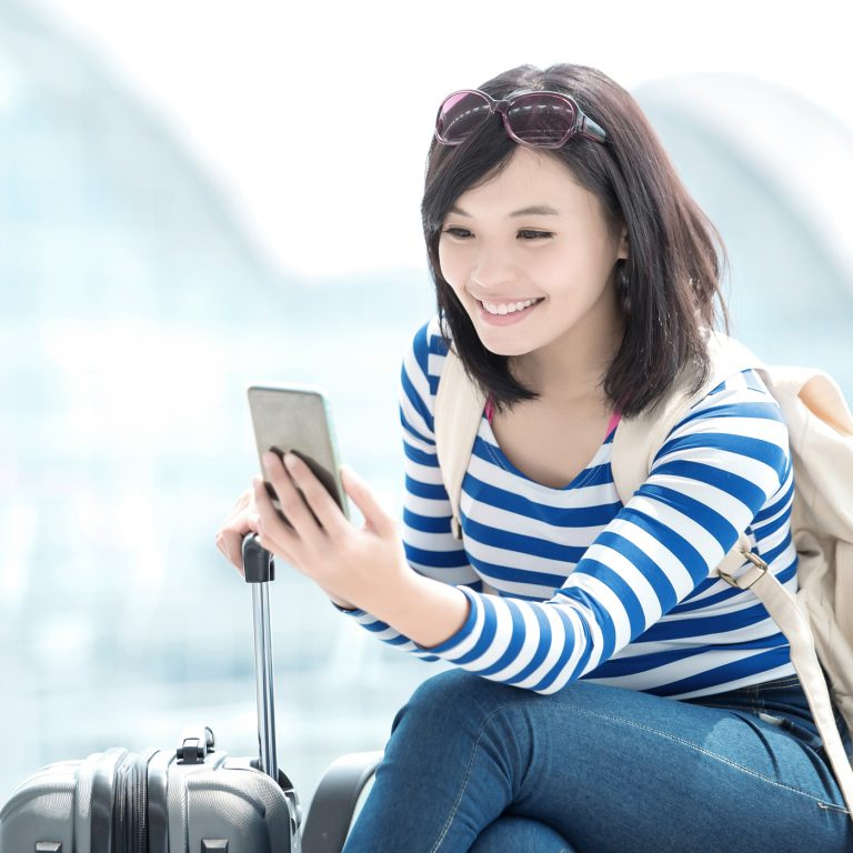 Woman using Voyage full digital commerce platform to book and pay, add ancillary, change flights and check-in on a responsive website or a native mobile app.